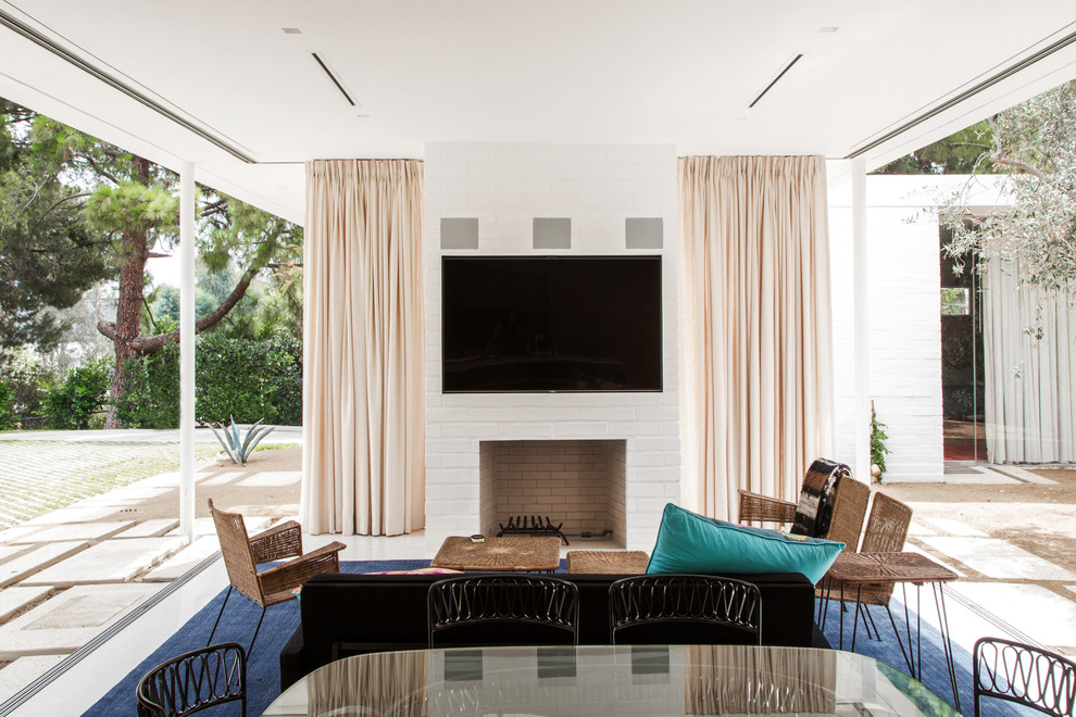 Example of a 1960s open concept family room design in Los Angeles with a standard fireplace and a wall-mounted tv