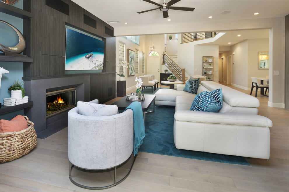 Inspiration for a huge coastal open concept light wood floor and beige floor family room remodel in Orange County with blue walls, a standard fireplace, a stone fireplace and a media wall