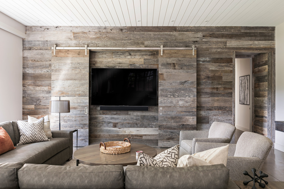 Example of a large country enclosed concrete floor and gray floor family room design in Charlotte with no fireplace and a concealed tv