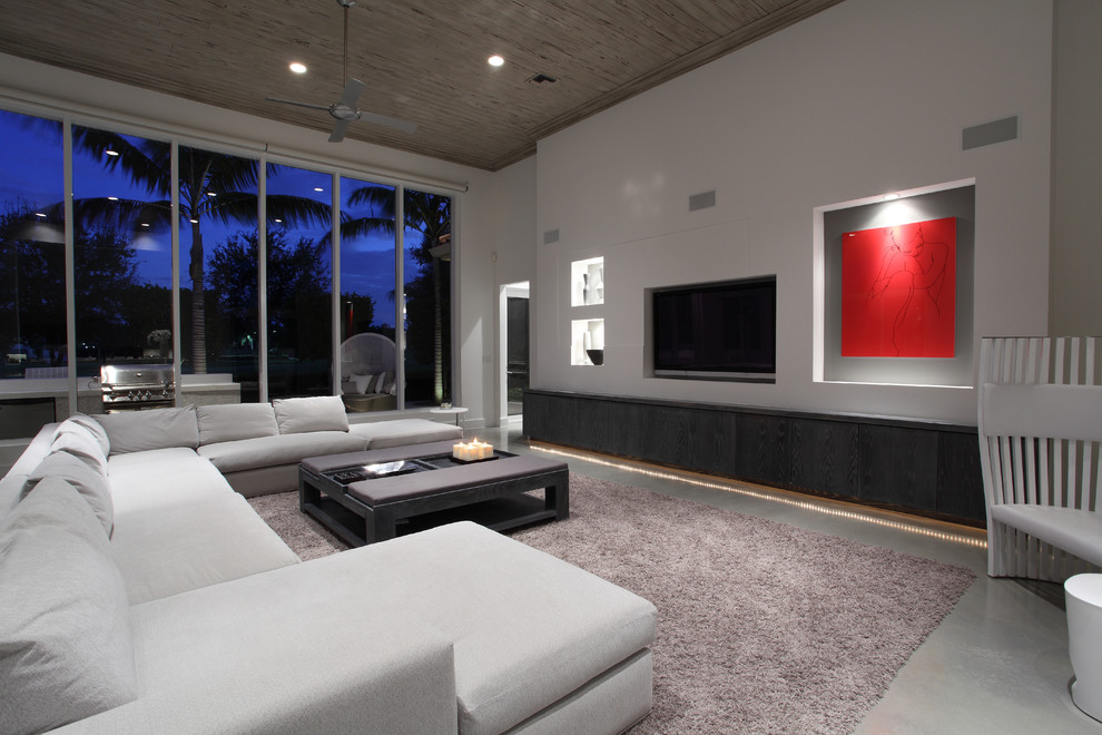 Example of a large minimalist concrete floor family room design in Miami with white walls, no fireplace and a media wall