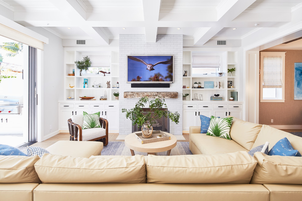 Beach style medium tone wood floor and brown floor family room photo in Los Angeles with white walls, a standard fireplace, a brick fireplace and a wall-mounted tv