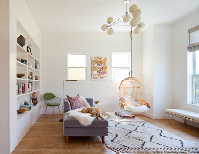 Inspiration for a mid-sized farmhouse enclosed medium tone wood floor and brown floor family room remodel in Denver with white walls, no fireplace and no tv