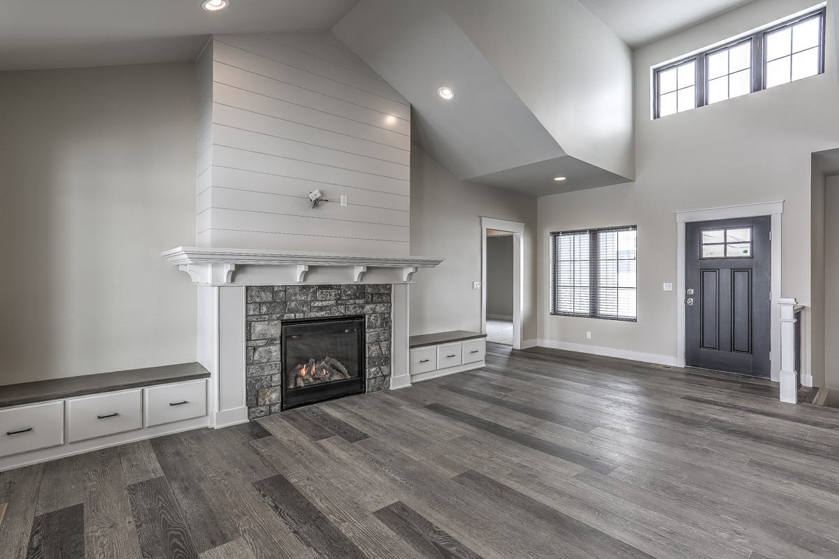 Example of a farmhouse open concept vinyl floor and gray floor family room design in Omaha with gray walls, a standard fireplace, a stone fireplace and a wall-mounted tv