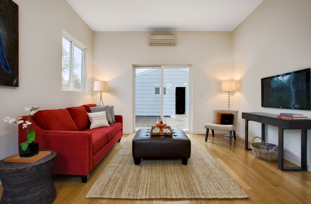 Inspiration for a contemporary medium tone wood floor family room remodel in Seattle with beige walls and a wall-mounted tv