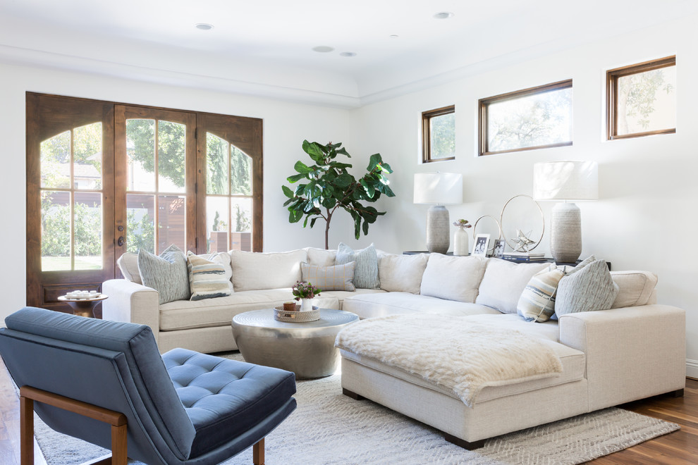 Family room - large mediterranean medium tone wood floor and brown floor family room idea in Los Angeles with white walls
