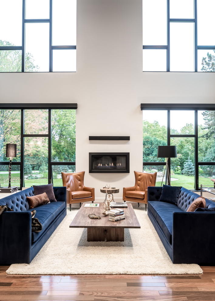 Large trendy open concept medium tone wood floor and beige floor family room photo in Minneapolis with white walls, a ribbon fireplace, a plaster fireplace and no tv