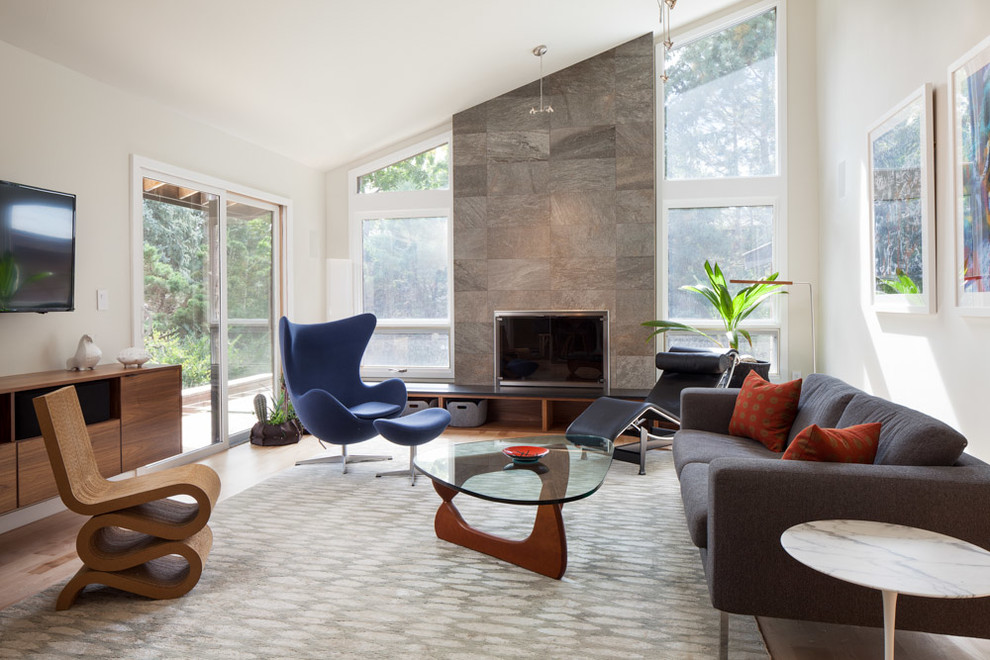Example of a mid-sized minimalist enclosed light wood floor and beige floor family room design in Denver with white walls, a standard fireplace, a concrete fireplace and a wall-mounted tv