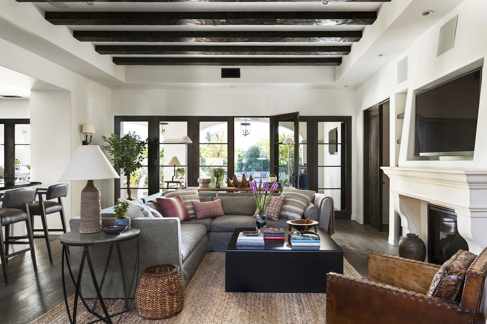 Example of a tuscan open concept dark wood floor family room design in Other with white walls, a standard fireplace and a media wall