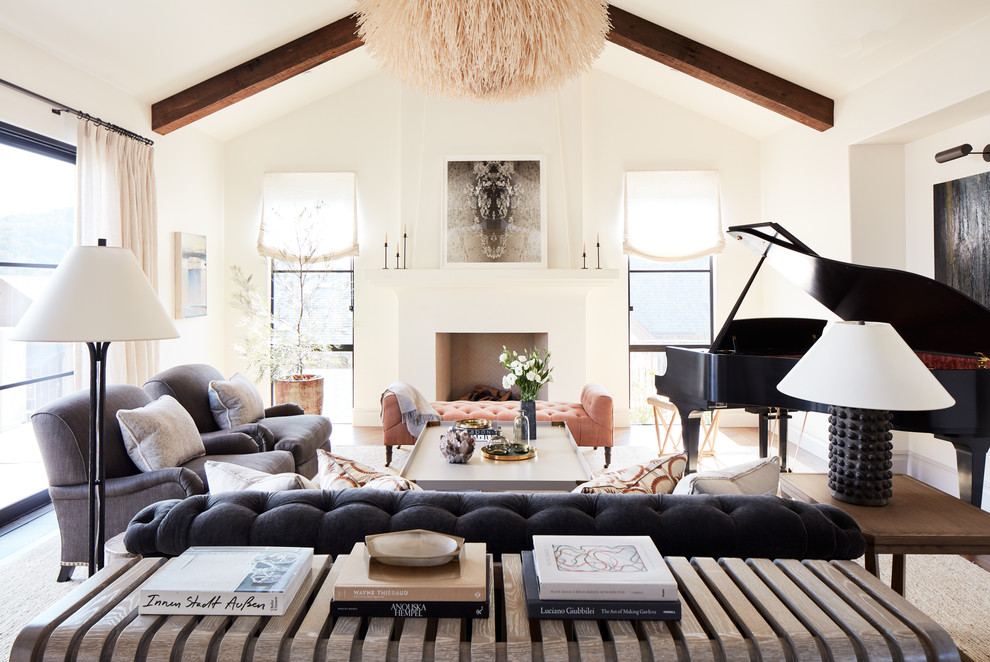 Example of a mid-sized tuscan open concept medium tone wood floor and brown floor family room design in San Francisco with a music area, white walls, a standard fireplace and a plaster fireplace