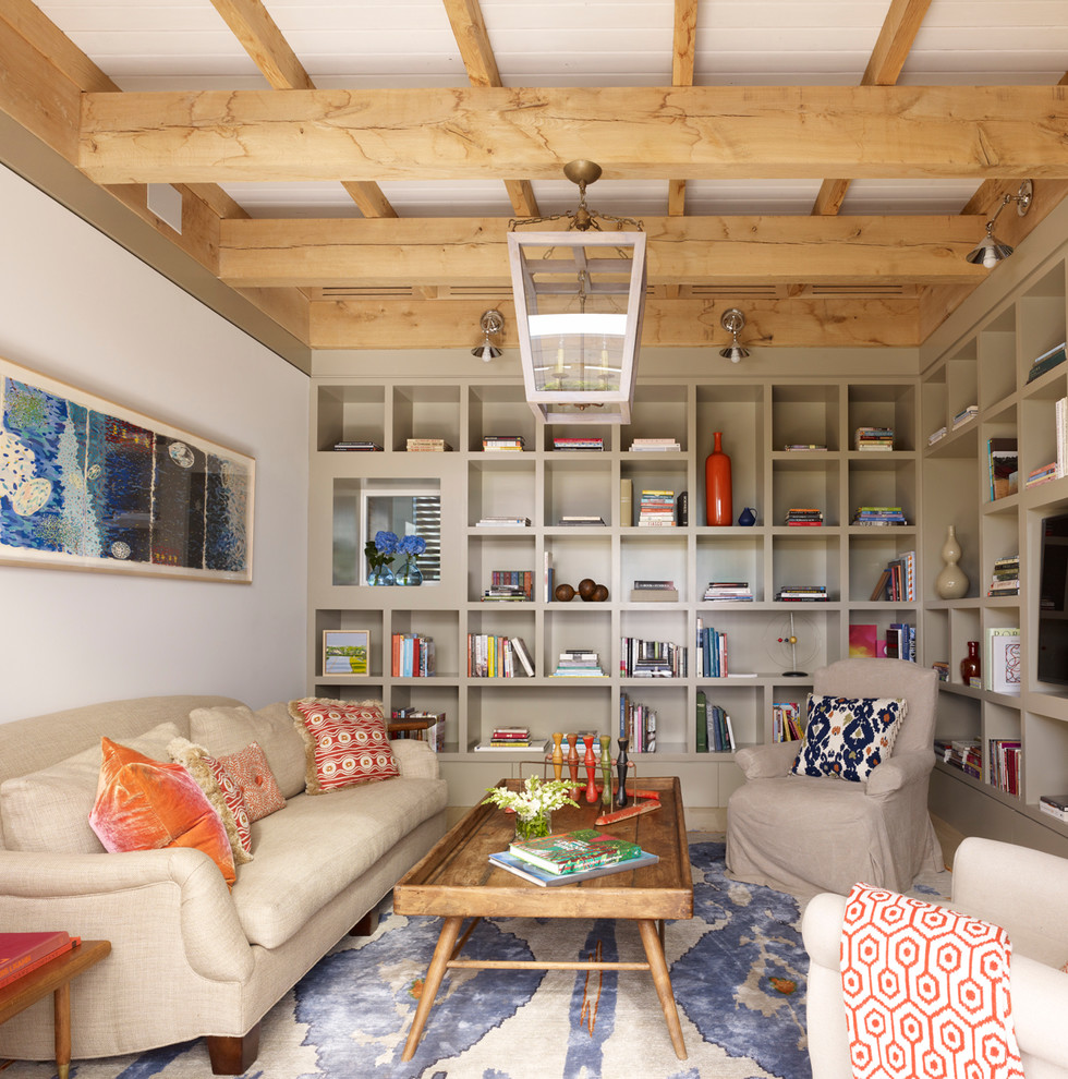 Family room - contemporary enclosed family room idea in New York with beige walls and a media wall