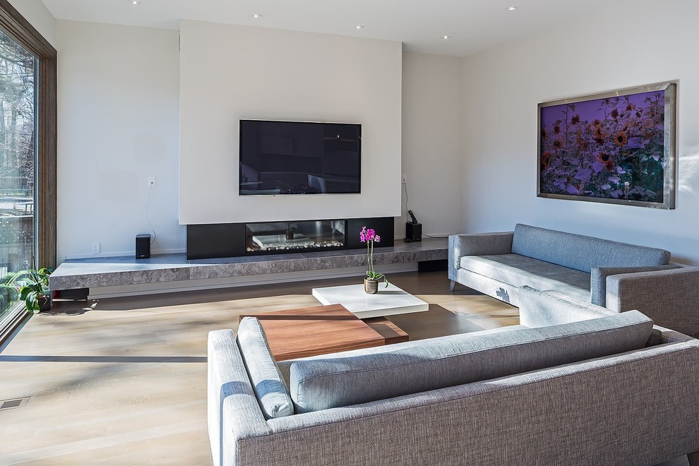 Inspiration for a large modern open concept medium tone wood floor and brown floor family room remodel in Toronto with white walls, a ribbon fireplace, a wall-mounted tv and a metal fireplace