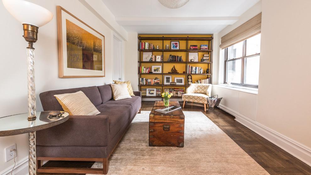 Imagen de sala de estar con biblioteca cerrada, minimalista, con paredes blancas y suelo de madera oscura