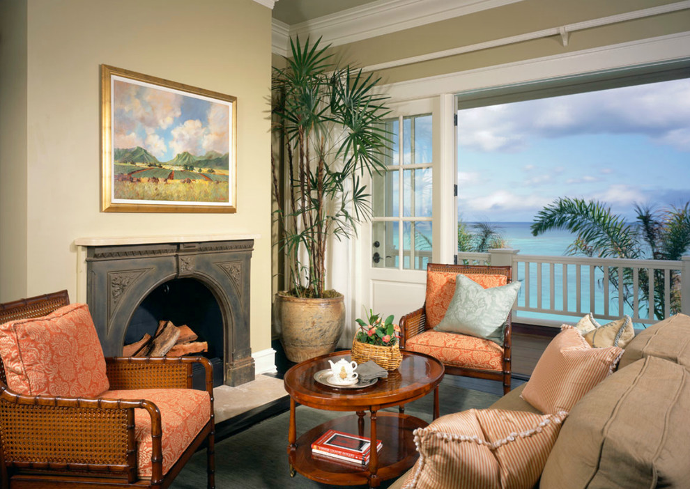 Example of an island style dark wood floor family room design in Tampa with beige walls, a standard fireplace and no tv