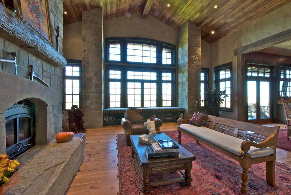Example of a mountain style family room design in Denver with a stone fireplace