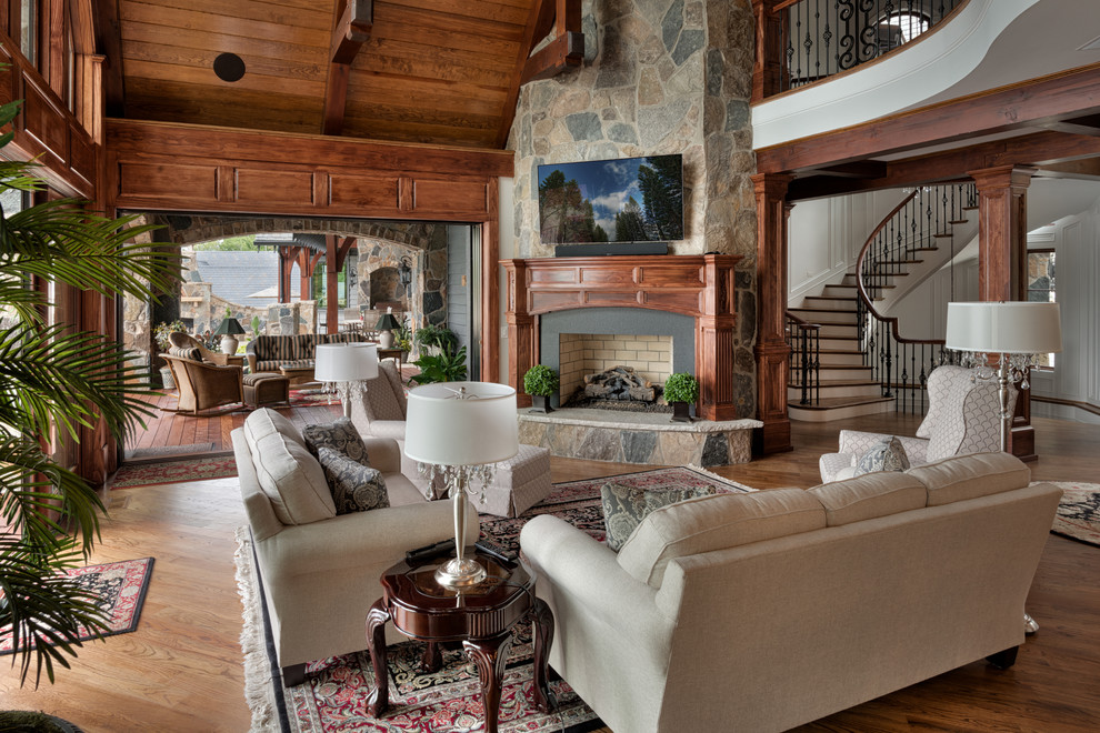 Elegant open concept dark wood floor family room photo in Other with a standard fireplace, a stone fireplace and a wall-mounted tv