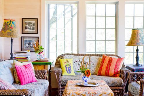 Sala de estar com móveis de vime, luminárias antigas pintadas à mão e almofadas coloridas