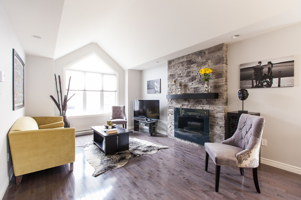Trendy medium tone wood floor family room photo in Other with gray walls, a standard fireplace, a stone fireplace and a tv stand
