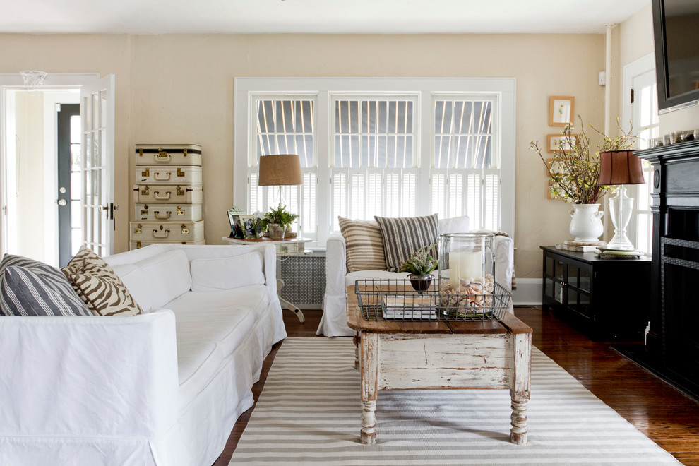 Family room - shabby-chic style dark wood floor family room idea in New York with beige walls, a standard fireplace and a wall-mounted tv