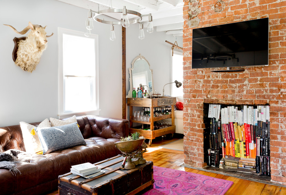 Example of an eclectic medium tone wood floor family room design in Providence with a bar, white walls and a wall-mounted tv
