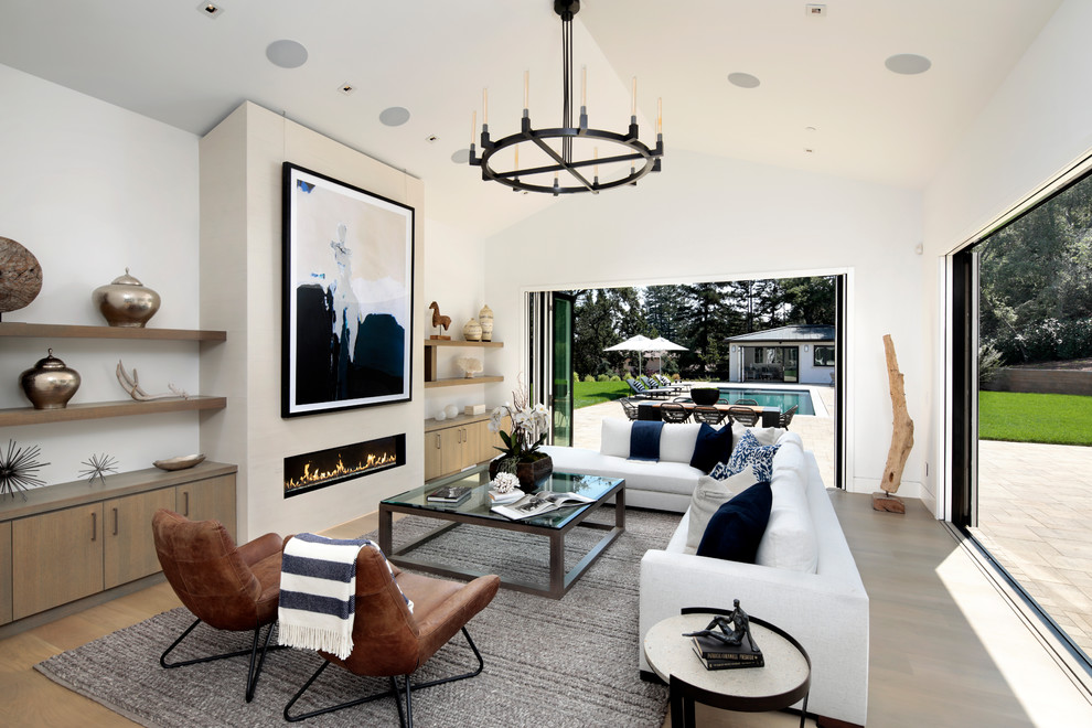 Family room - transitional open concept light wood floor and brown floor family room idea in San Francisco with white walls and a ribbon fireplace