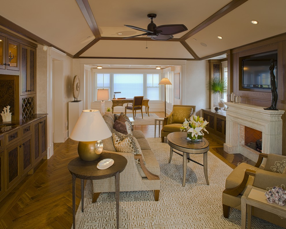 Trendy medium tone wood floor family room photo in Philadelphia with beige walls, a standard fireplace, a stone fireplace and a wall-mounted tv