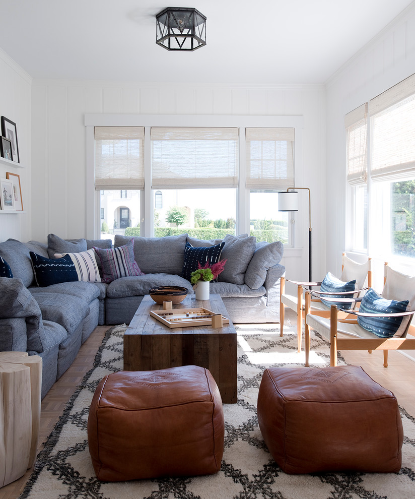 Inspiration for a coastal medium tone wood floor family room remodel in New York with white walls