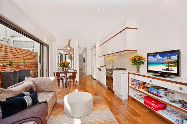 Trendy open concept medium tone wood floor family room photo in Sydney with white walls and a tv stand