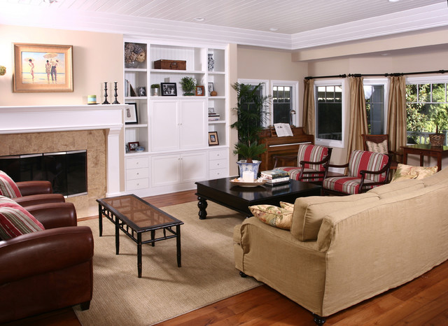 Example of a classic medium tone wood floor family room design in Orange County with beige walls, a standard fireplace and a concealed tv