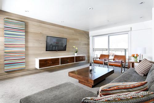 Télévision grand écran fixée au mur dans un salon sobre et moderne