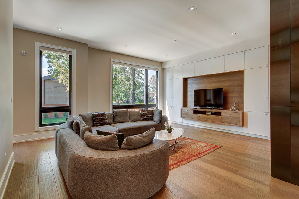 Inspiration for a small modern enclosed light wood floor and beige floor family room remodel in Toronto with beige walls, no fireplace and a tv stand
