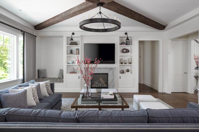 Modelo de sala de estar tradicional renovada con paredes blancas, suelo de madera oscura, chimenea tradicional, marco de chimenea de piedra y televisor colgado en la pared