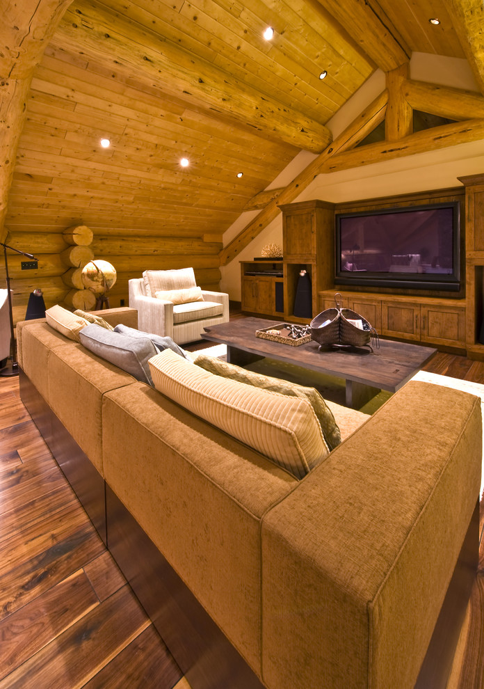Mountain style medium tone wood floor family room photo in Vancouver with beige walls and a media wall