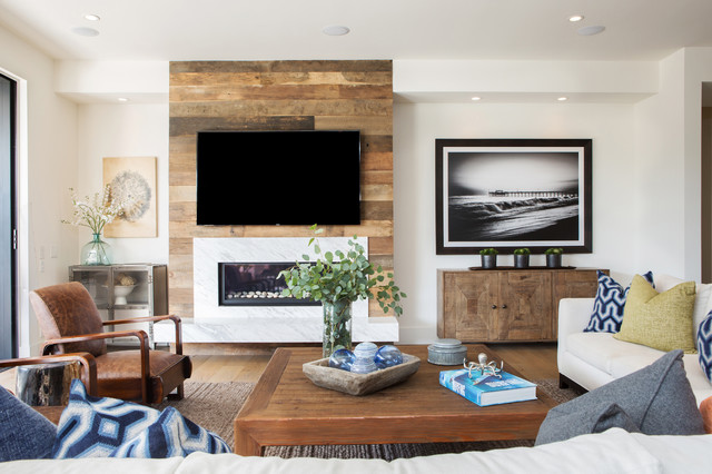 Coastal family room photo in Orange County with white walls, a ribbon fireplace, a wall-mounted tv and a stone fireplace