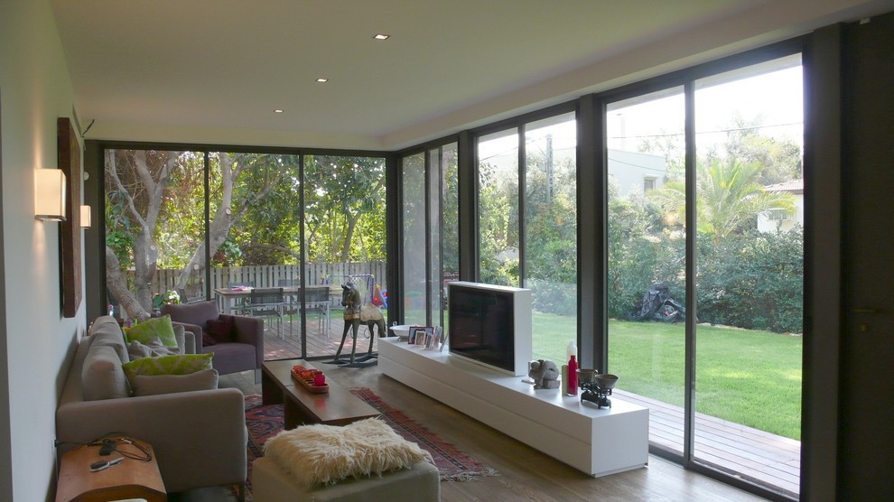 Inspiration for a contemporary medium tone wood floor family room remodel in Tel Aviv with beige walls and a tv stand