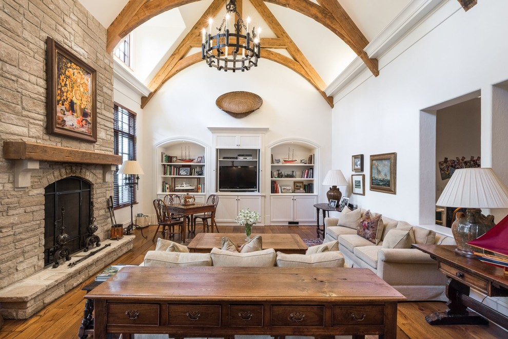 Example of a classic medium tone wood floor family room design in Atlanta with white walls, a standard fireplace, a stone fireplace and a media wall