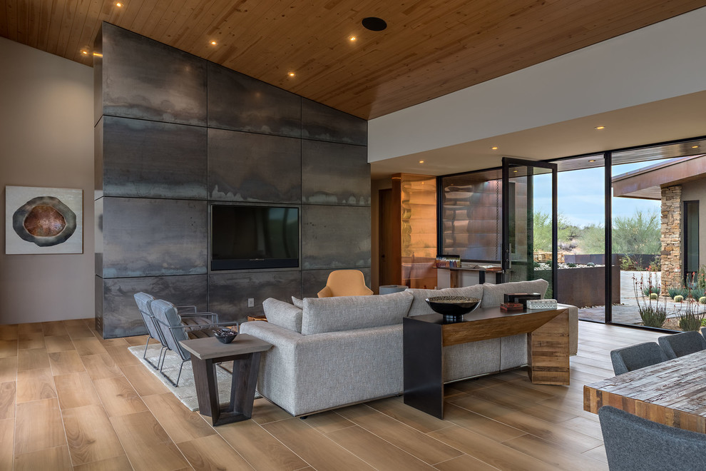 Example of a mid-sized trendy open concept porcelain floor and brown floor family room design in Phoenix with gray walls and a media wall
