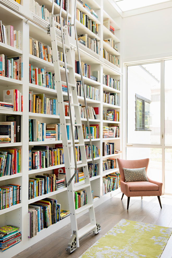 Mid-sized trendy dark wood floor and brown floor family room library photo in Los Angeles with white walls