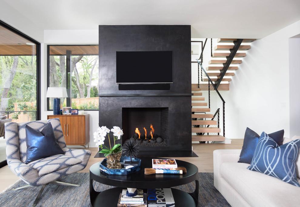 Foto de sala de estar abierta, actual, de tamaño medio, con suelo de madera clara, todas las chimeneas, marco de chimenea de hormigón, televisor colgado en la pared, suelo beige y paredes negras