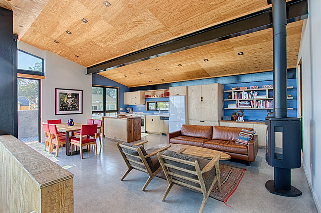 Family room - small beach style open concept concrete floor and gray floor family room idea in San Francisco with blue walls, a wood stove, a metal fireplace and no tv