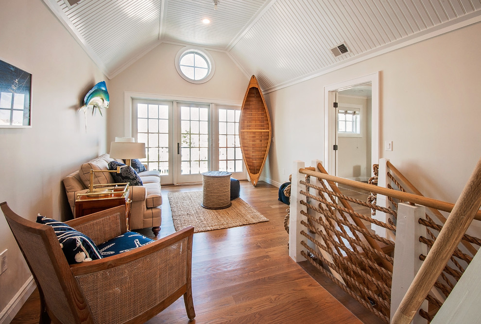 Inspiration for a coastal medium tone wood floor and brown floor family room remodel in New York with beige walls