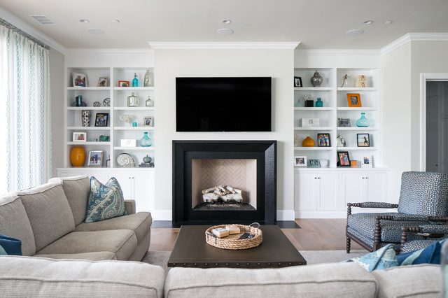 Inspiration for a transitional light wood floor family room remodel in Orange County with a standard fireplace, a wall-mounted tv and a plaster fireplace