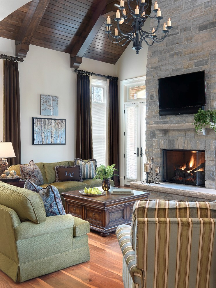 Inspiration for a timeless medium tone wood floor family room remodel in St Louis with beige walls, a standard fireplace, a stone fireplace and a wall-mounted tv