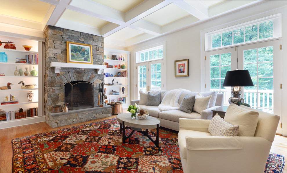 Large elegant enclosed medium tone wood floor and brown floor family room photo in New York with beige walls, a standard fireplace and a stone fireplace