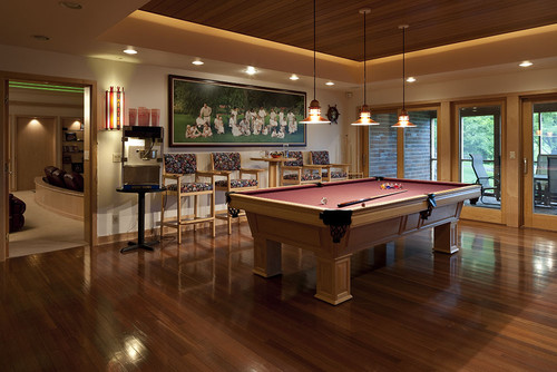 Traditional styled game room with a billiard table and four bar stools with arms and pub tables
