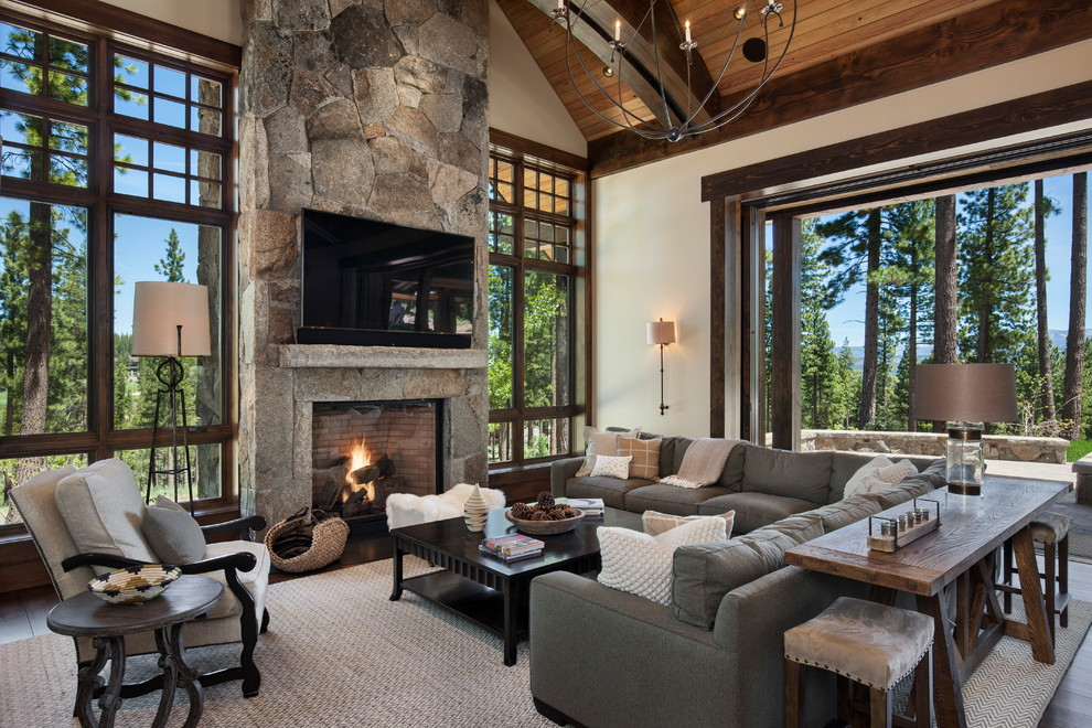 Example of a large mountain style open concept dark wood floor family room design in Sacramento with white walls, a standard fireplace, a stone fireplace and a wall-mounted tv