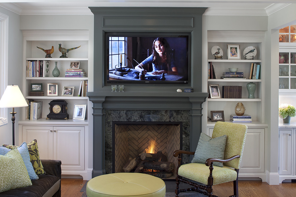 Inspiration for a timeless medium tone wood floor family room remodel in San Francisco with gray walls, a standard fireplace, a wall-mounted tv and a wood fireplace surround