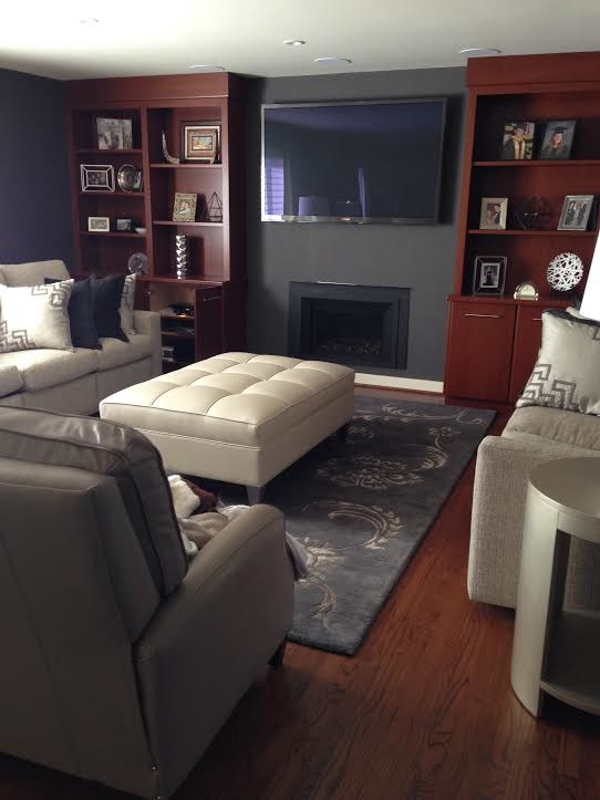 Example of a mid-sized classic enclosed medium tone wood floor and brown floor family room design in Philadelphia with gray walls, a standard fireplace, a plaster fireplace and a wall-mounted tv