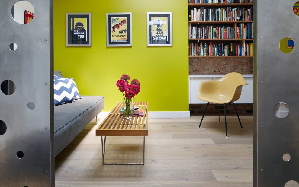 Trendy enclosed light wood floor family room library photo in New York with green walls