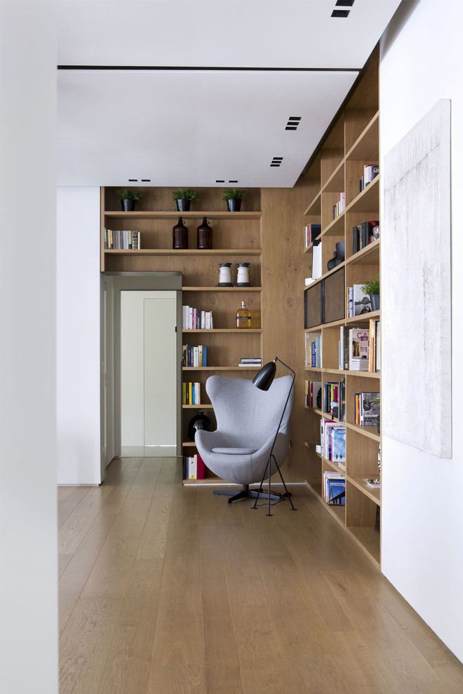 Family room library - modern light wood floor family room library idea in Turin with white walls
