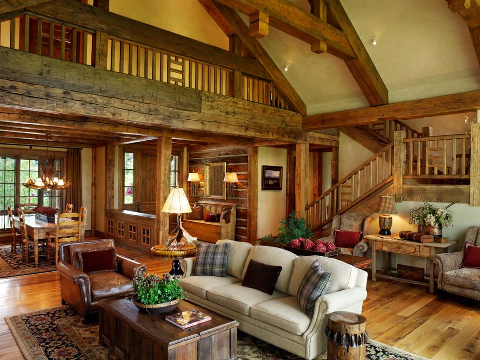 Imagen de sala de estar abierta, rural, extra grande, con paredes beige, suelo de madera en tonos medios y suelo multicolor